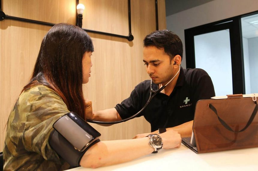 Speedoc chief executive officer Dr Shravan Verma checking a patient's blood pressure and heart rate in her home.