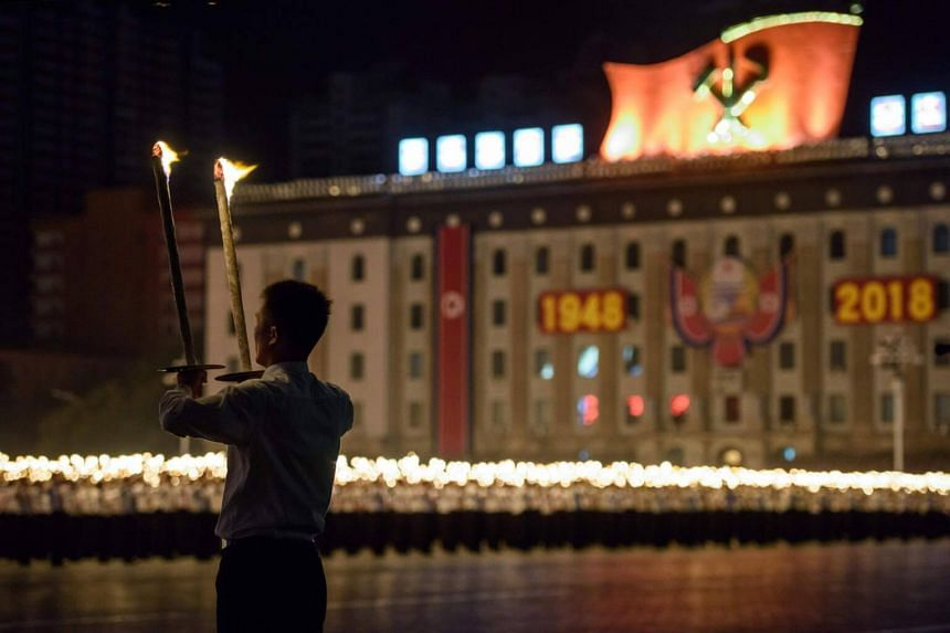 A participant looks on as others perform in a torch parade on Kim Il Sung square in Pyongyang, on Sept 10, 2018.
