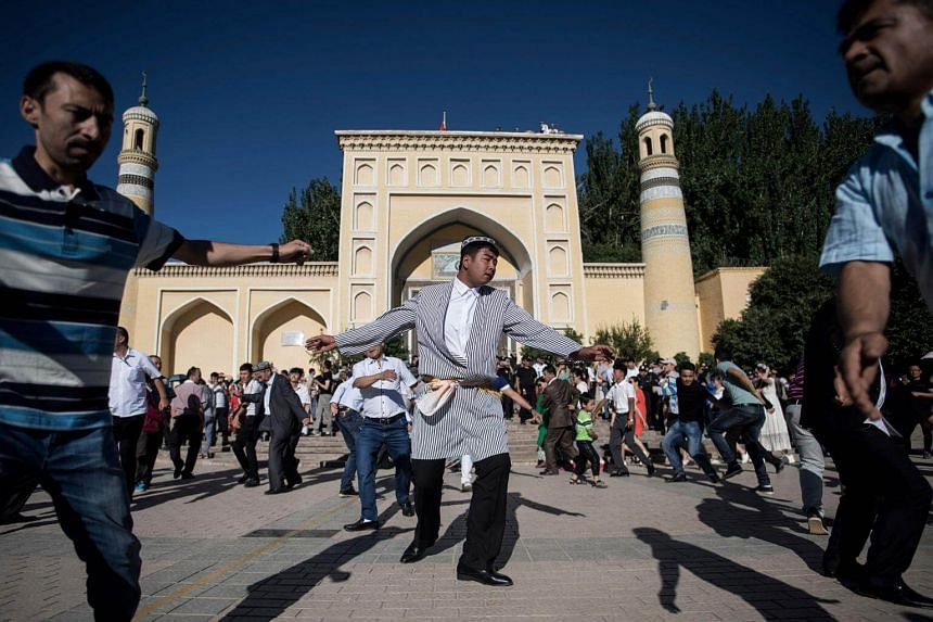 Men dancing in front of the Id Kah Mosque after morning prayer in China's Xinjiang Uighur Autonomous Region, on June 26, 2017.