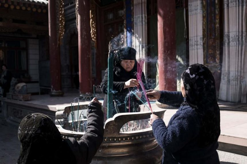 Ethnic Hui Muslim women pray in a courtyard at a religious site in Linxia, China's Gansu province.