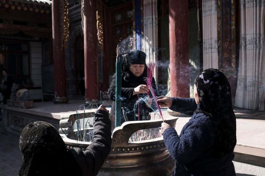 Ethnic Hui Muslim women pray in a courtyard at a religious site in Linxia, China's Gansu province.
