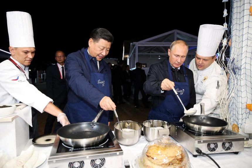 Russian President Vladimir Putin and Chinese President Xi Jinping making pancakes during a visit to the Far East Street exhibition in Vladivostok, Russia, on Sept 11, 2018.