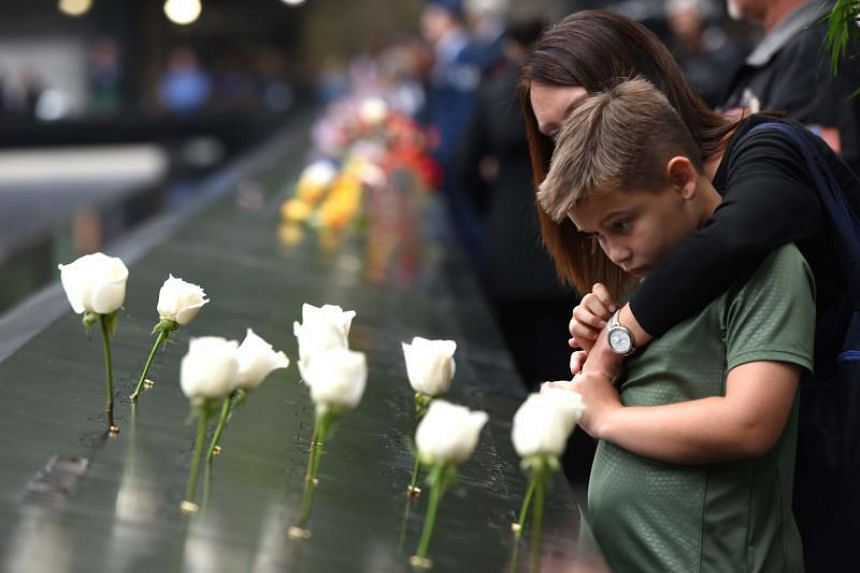 A young boy and his mother look down into the South Pool during observances held on the 17th anniversary of the 9/11 terror attacks, at the Ground Zero memorial site in New York, on Sept 11, 2018.