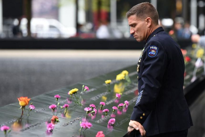 A Port Authority Police Officer looks down into the South Pool during observances held on the 17th anniversary of the 9/11 terror attacks at the annual ceremony at the Ground Zero memorial site, in New York, on Sept 11, 2018.