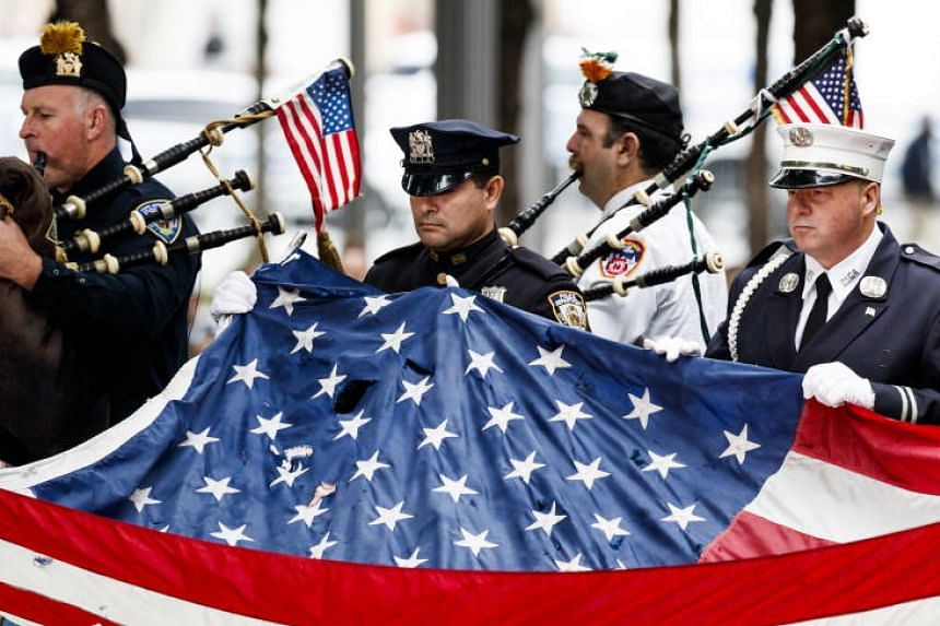 Firefighters and police officers carry an American flag that once flew over the World Trade Center at the 9/11 Memorial during ceremonies marking the 17th anniversary of the 9/11 terrorist attacks in New York, on Sept 11, 2018.