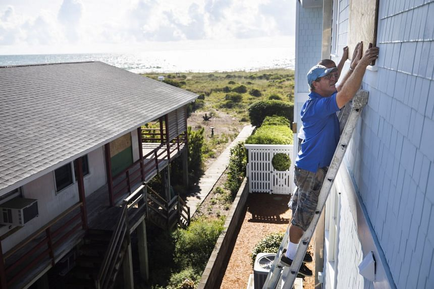 Butch Beaudry places a wooden plank over the window of an oceanfront home, less than two days before Hurricane Florence is expected to strike Wrightsville Beach, North Carolina.