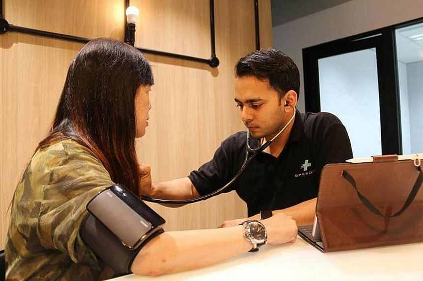Speedoc chief executive officer Shravan Verma checking a patient's blood pressure and heart rate in her home. The medical service provider is among four that have joined the MOH's regulatory sandbox for telemedicine, allowing them to offer services t