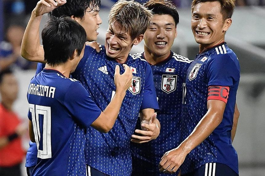 Japan defender Sho Sasaki (centre) and his team-mates celebrating their first goal against Costa Rica during their friendly in Osaka.