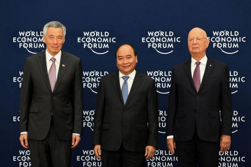 Singapore Prime Minister Lee Hsien Loong with Vietnamese Prime Minister Nguyen Xuan Phuc and Professor Klaus Schwab, founder and executive chairman of the World Economic Forum, at the welcoming ceremony at the National Convention Centre in Hanoi, Vie