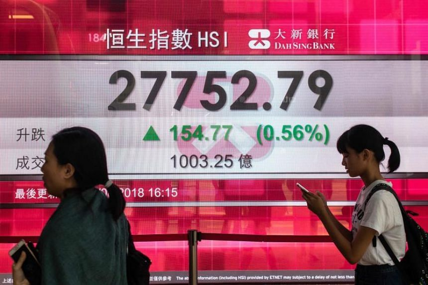 Pedestrians walk past a stocks display after the close of trading in Hong Kong, on Aug 21, 2018.