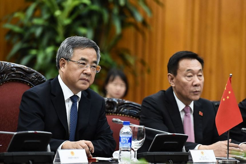 """Chinese Vice-Premier Hu Chunhua (left) suggests that countries should """"categorically reject"""" protectionism in trade."""