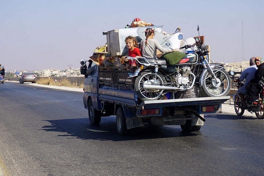 Syrian children riding in the back of a truck loaded with furniture and a motorcycle, driving along the main Damascus-Aleppo highway near the town of Saraqib in Syria's mostly rebel-held northern Idlib province, on Sept 11, 2018.