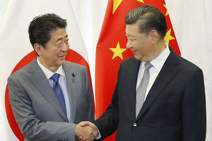 Japan's Prime Minister Shinzo Abe (left) shakes hands with China's President Xi Jinping prior to their bilateral meeting in Vladivostok, on Sept 12, 2018.