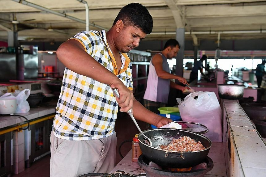 Residents cooking at Changi Lodge 2, which won an award yesterday for providing comfortable living spaces for foreign workers.