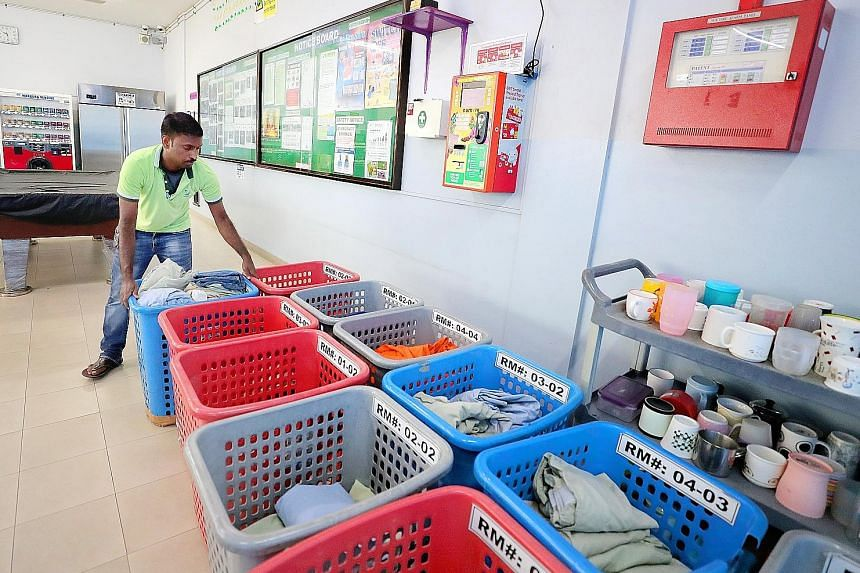 Above: Utoc's dormitory in Boon Lay can house about 240 workers Left: Dormitory assistant Paliyandi Meganathan, 34, arranges the cleaned garments for workers to collect. Dorm residents do not have to pay extra for laundry service. Left: Welder Sheikh