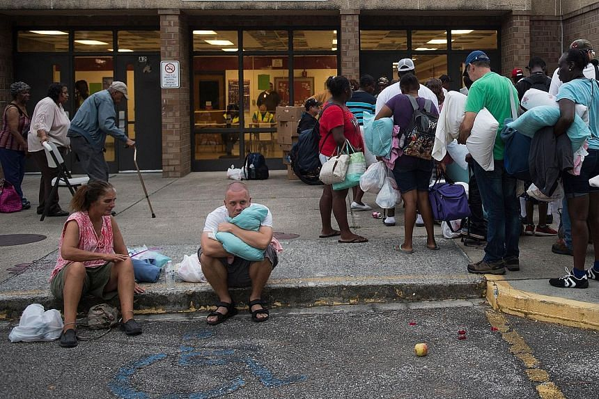 People waiting to enter a hurricane shelter in North Carolina on Tuesday. Federal Emergency Management Agency administrator Brock Long has warned that communities could lose electricity for weeks.