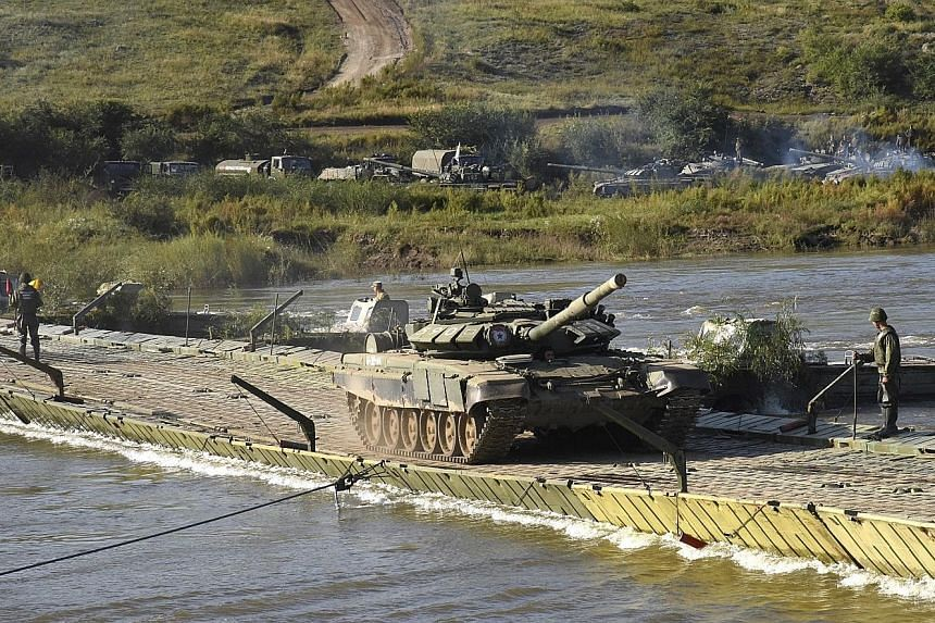 A Russian Ministry of Defence photo shows military equipment, tanks and motorised rifle divisions crossing the Onon river during Vostok-2018 yesterday.