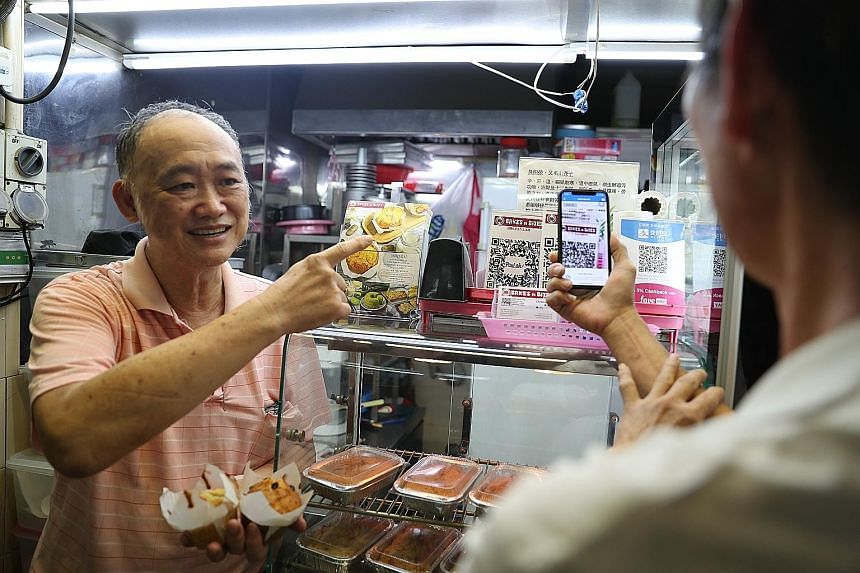 Hawker Christopher Lau with a customer making payment using the Nets QR code at his bakery stall at Old Airport Road Food Centre. Mr Lau's stall has three QR codes to accept payments from three different e-wallets. He says he is looking forward to Ne