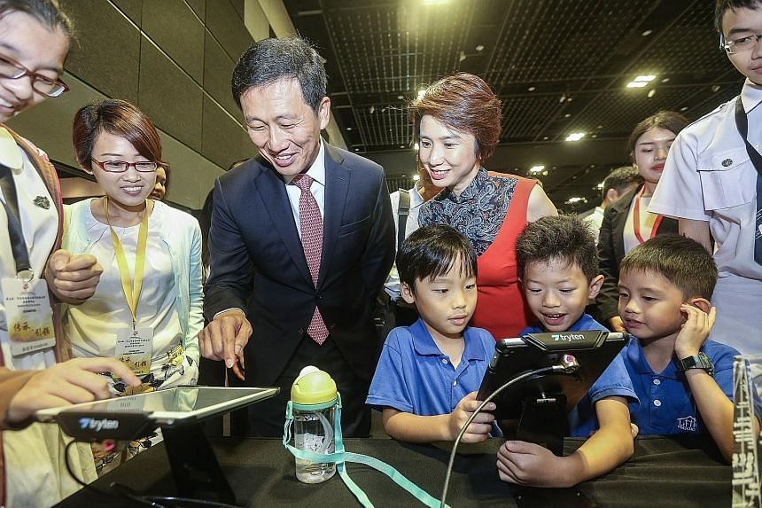 Education Minister Ong Ye Kung and Senior Parliamentary Secretary for Education and Manpower Low Yen Ling (right) checking out one of the Chinese apps that won an award in an app development contest organised by SCCL. Mr Ong gave out the awards yeste