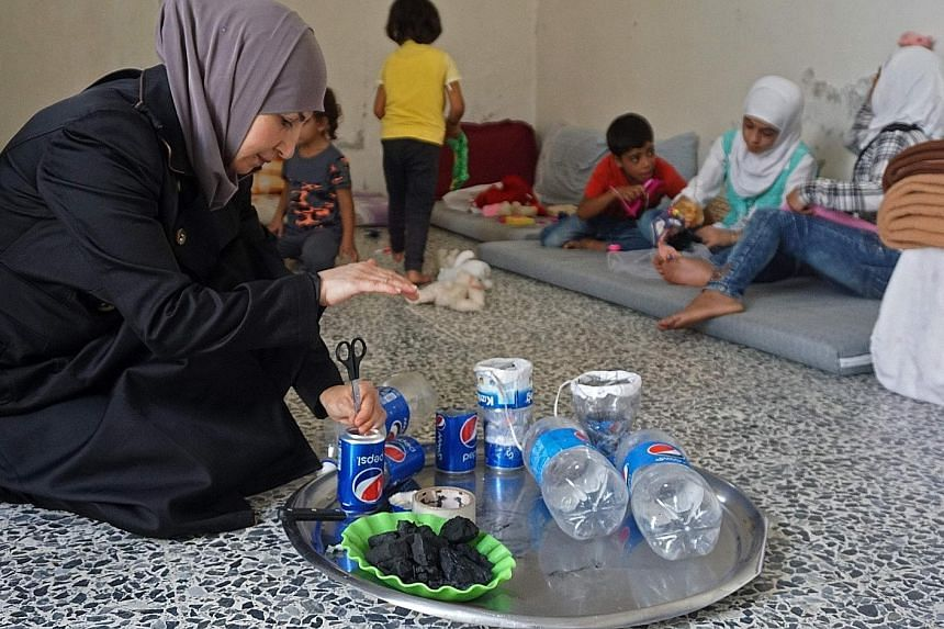 Ms Um Majid making improvised gas masks yesterday in her home in Binnish in Syria's rebel-held northern Idlib province as part of preparations for upcoming raids. Fearing the advance of government forces and their allies to retake Idlib province, fam