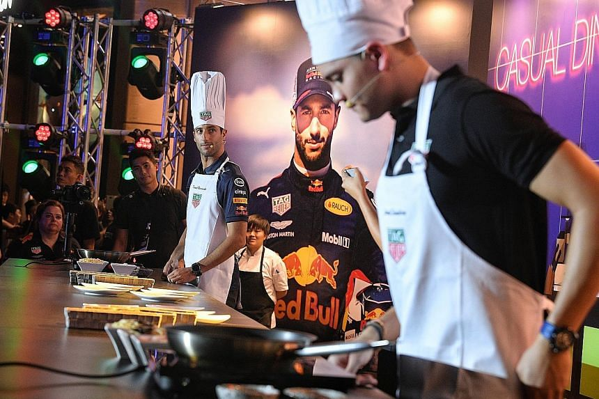 Red Bull's Australian F1 driver Daniel Ricciardo and Singapore's Olympic swimming champion Joseph Schooling pictured during their cook-off at a Tag Heuer event yesterday at Ion Orchard.