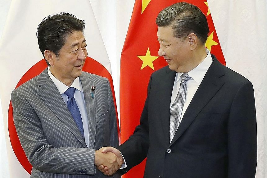 """Japan's Prime Minister Shinzo Abe (left) and China's President Xi Jinping on the sidelines of the fourth annual Eastern Economic Forum in Vladivostok. Mr Xi said in his meeting with Mr Abe yesterday that China-Japan ties have """"entered a normal course"""