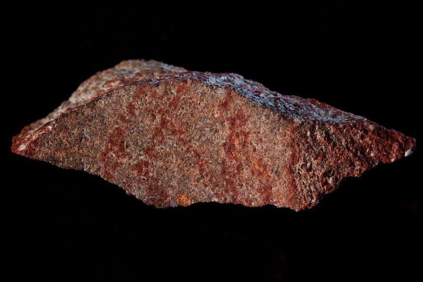A stone flake discovered in South Africa's Blombos Cave showing red ochre markings that archaeologists say represent one of the oldest-known examples of human drawings.