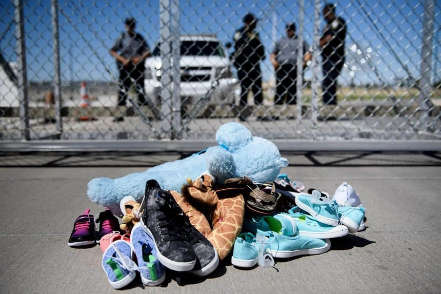 Security personnel standing before shoes and toys left at the Tornillo Port of Entry in Texas, where minors crossing the border without proper papers have been housed after being separated from adults, on June 21, 2018.