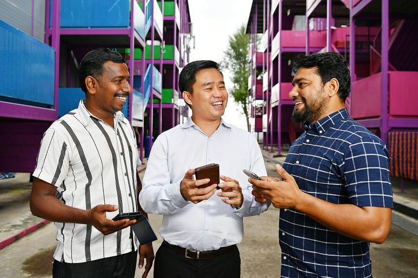 S11 Dormitories' business development director Lawrence Lee using the company's digital platform with foreign workers Nachiyappan Mohan (far left) and Khaladur Rahman Omar Ali. The platform allows residents of the firm's dormitories to give feedback