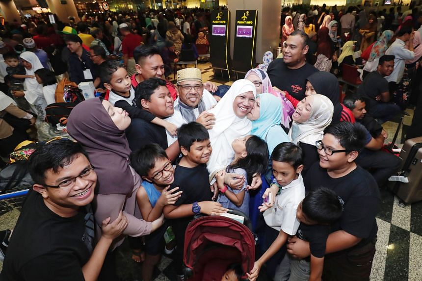 Returning Haj pilgrims Abdullah Ahmad (centre with a gold songkok), 63, and his wife Safiah Ahmad (in a white tudung), 60, receiving a group hug from their family members at Changi Airport Terminal 3 yesterday. The retirees were among more than 280 p