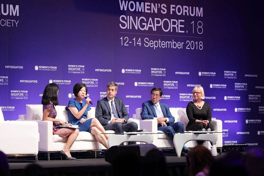 Ms Sim Ann, Senior Minister of State for Communications and Information, and Culture, Community and Youth (holding microphone) speaking at a plenary session at the Women's Forum Singapore yesterday. The three-day forum has lined up more than 20 sessi