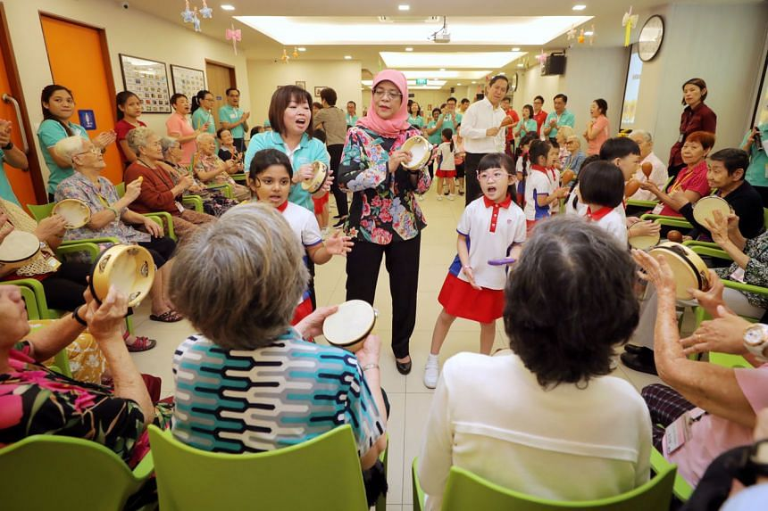 President Halimah Yacob (at centre) joined about 30 seniors and 21 kindergarten pupils at Sparkle Care @ Yew Tee for an activity-filled programme that promotes inter-generational understanding yesterday. Participants joined in with tambourines or oth