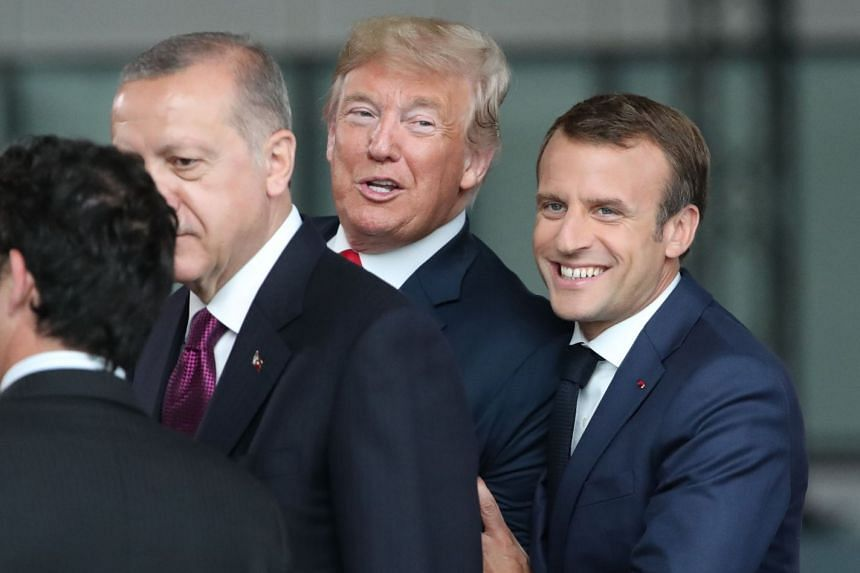 French President Emmanuel Macron (right) joking with US President Donald Trump (centre) at a Nato summit in July 2018.