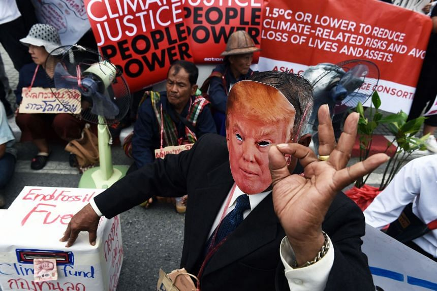 An  activist wearing a Donald Trump face-mask takes part in a protest amid climate talks in Bangkok on Sept 8, 2018.