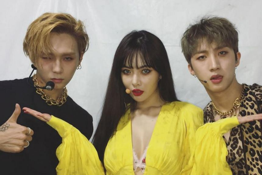 South Korean pop singer HyunA (centre) and her boyfriend Pentagon's E'Dawn (left) were removed from their label Cube Entertainment on Thursday (Sept 13) after they came out publicly as a couple.