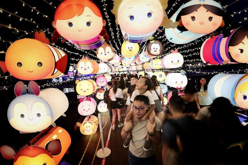Six-year-old Gideon, riding on the shoulders of his father, Mr Michael Lee, 37, being drawn to the Disney Tsum Tsum lanterns at VivoCity's Sky Park yesterday. More than 2,000 of the lanterns are on display there until Sept 30, as part of the mall's M