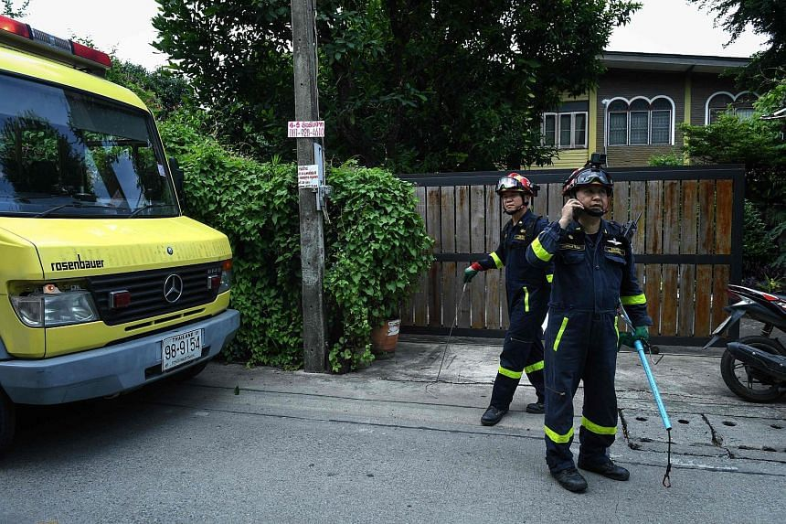 Thai firefighter and snake expert Sutaphong Suepchai (right) responding to an emergency call to trap and capture a snake from a home in Bangkok.