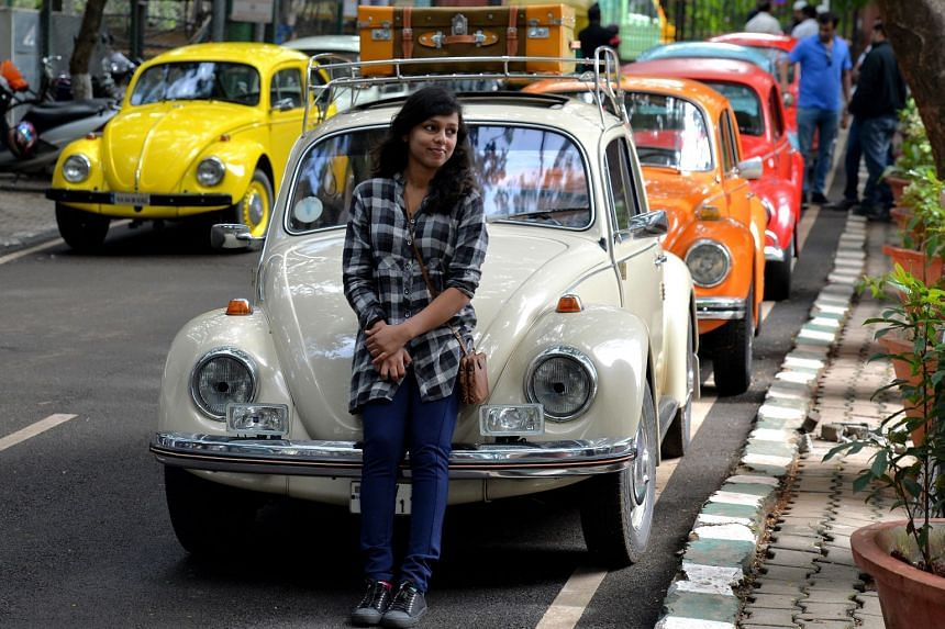 A girl stands in front of a vintage Volkswagen Beetle car during a Beetle rally in Bangalore, India, in June 2018.
