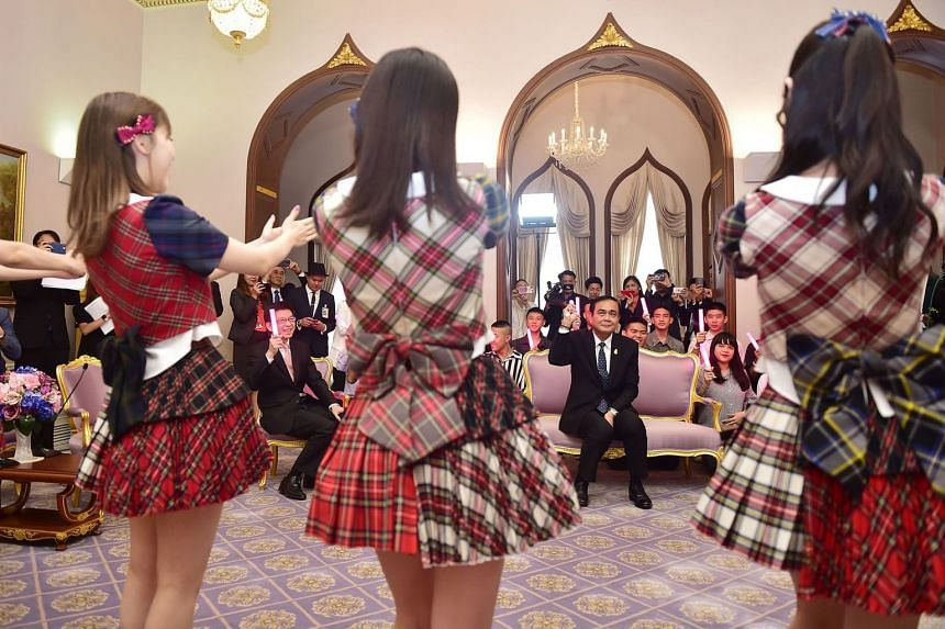 Thailand's Prime Minister Prayut Chan-O-Cha (right, seated) watching members of the Japanese girl pop sensation AKB48 perform at the Government House in Bangkok.