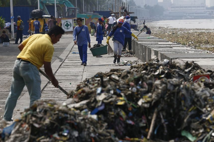 Workers collecting trash and debris along the shore of Manila Bay as part of typhoon precautions in Manila, Philippines, on Sept 13, 2018.