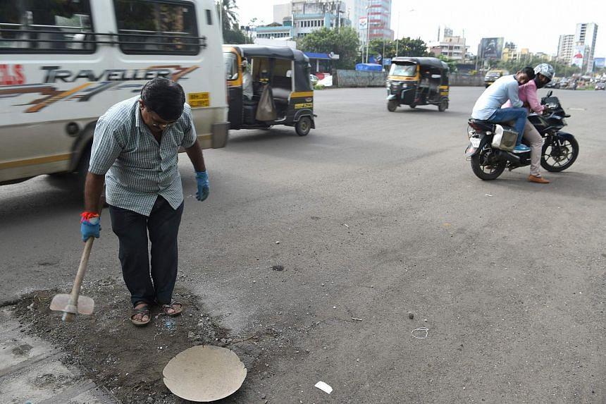 Indian businessman Dadarao Bilhore filing up a pothole on the Western Express highway in Mumbai, India, on Aug 29, 2018.