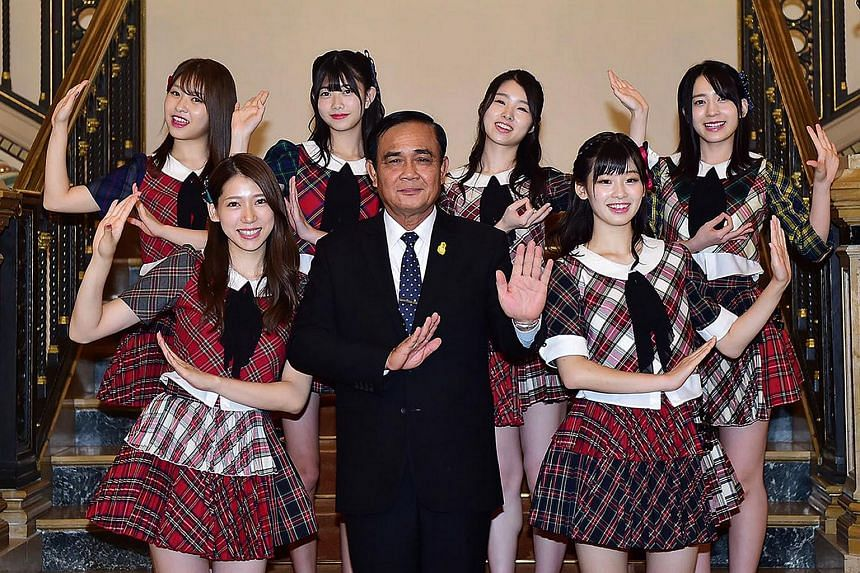 Thai PM Prayut Chan-o-cha (centre) posing for pictures with six members of Japanese pop group AKB48, before a meeting at the Government House in Bangkok, Thailand, on Sept 13, 2018.