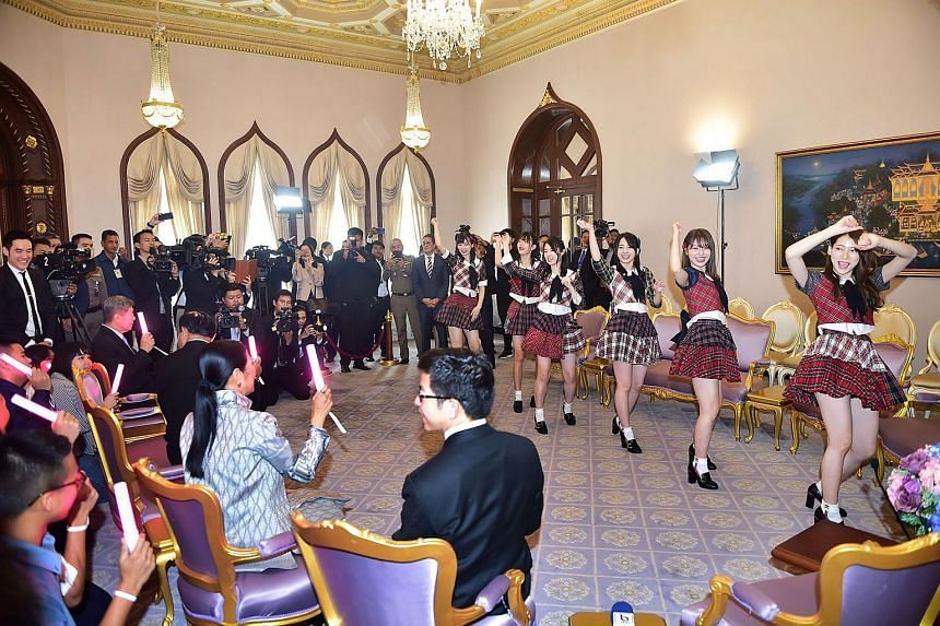 Thai PM Prayut Chan-o-cha (seated, second, left) watching members of the Japanese pop sensation AKB48 perform at the Government House in Bangkok.