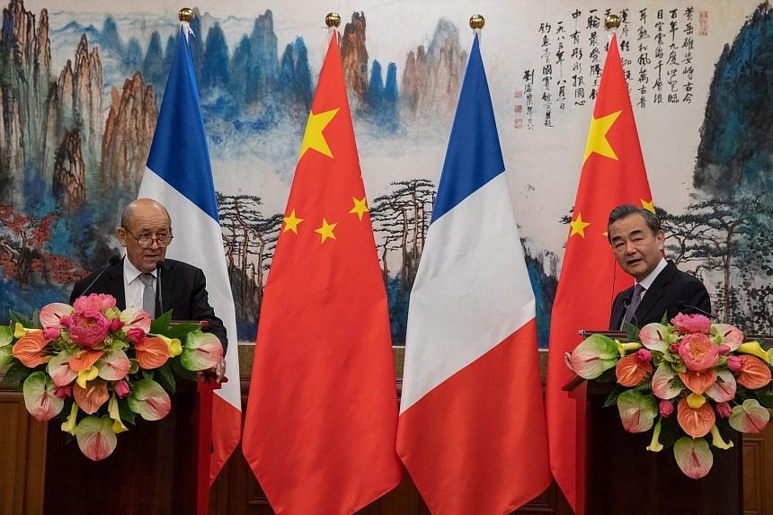 French Foreign Minister Jean-Yves Le Drian (left) with Chinese Foreign Minister Wang Yi at a joint press conference following their meeting at Diaoyutai State Guesthouse in Beijing, China, on Sept 13, 2018.