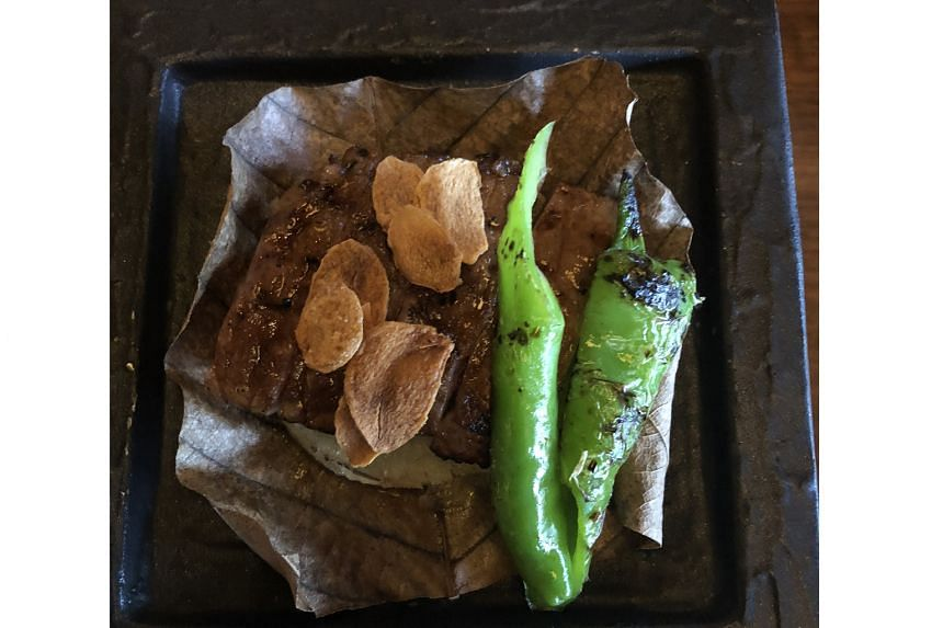 Beef is grilled on a leaf in a ceramic plate placed above a small charcoal stove