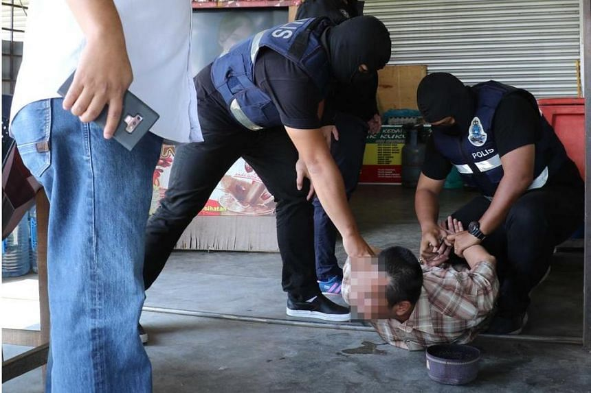 Anti-terrorism division officers pinning a suspected militant down.