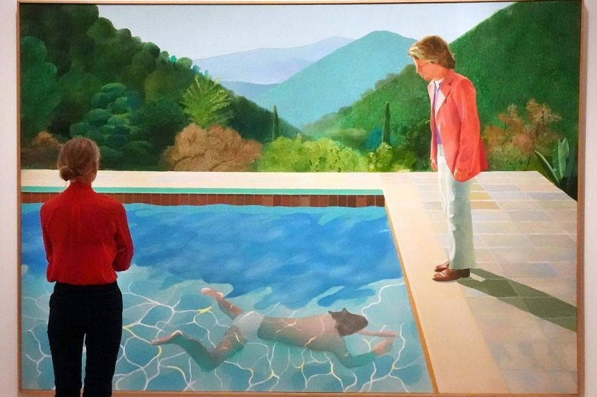 """A woman looks at David Hockney's """"Portrait of an Artist (Pool with Two Figures)"""" during a press preview."""