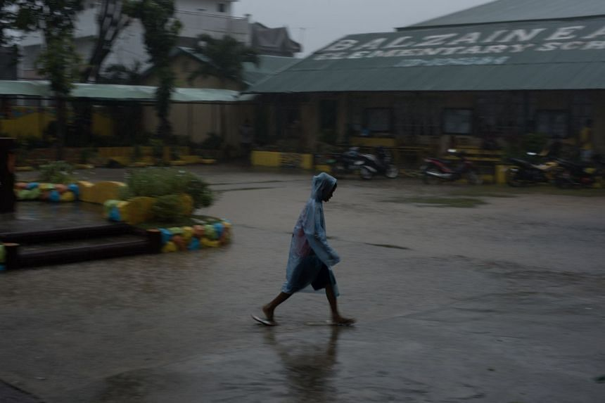 A boy walking in heavy rainfall ahead of Mangkhut's arrival in Tuguegarao, Cagayan province.