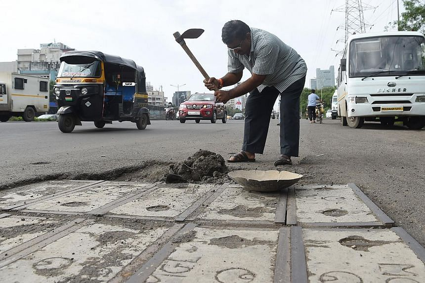 Mr Dadarao Bilhore filling up a pothole in Mumbai last month. He decided to fix the city's shoddy roads after his 16-year-old son was killed in an accident involving a pothole.