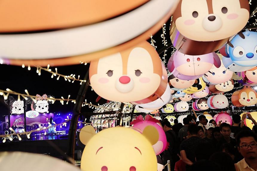 VivoCity's Sky Park: Crowds pose with Disney's Mickey and Minnie installation (left) and more than 2,000 Disney Tsum Tsum lanterns light up the night sky (right). Gardens by the Bay: The Sky Lantern Dreams at the Scented Walk (above) and The Phoenix